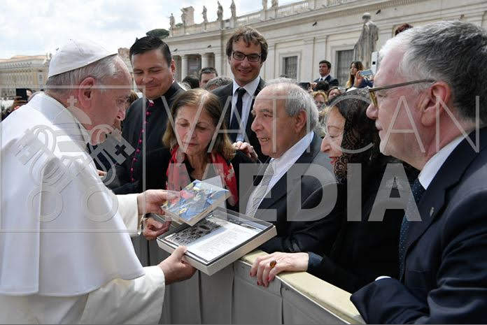 Giuseppe Biagi presents Pope Francis with a photo from the memorial ceremony.